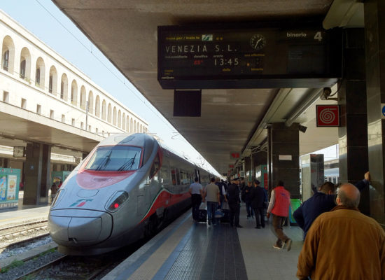 The picture shows a train on a track at Venice Train Station. From this page you can Book a private transfer from Venice Train Station to your hotel